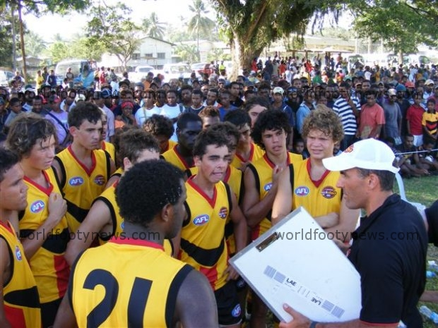 The Boomerangs listen to the coach in Lae, with a big crowd looking on